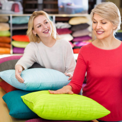 Adult girl and aged mother choosing pillows in home textile shop